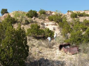 The rusted old car and the guys on the side of the canyon.
